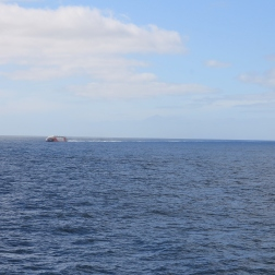 Rechts neben dem Katamaran schemenhaft der Vulkan El Teide auf Teneriffa