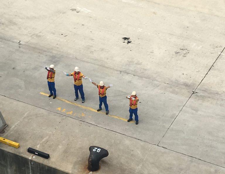Hafenarbeiter verabschieden winkend die Fähre Panstar Dream am Kai in Busan