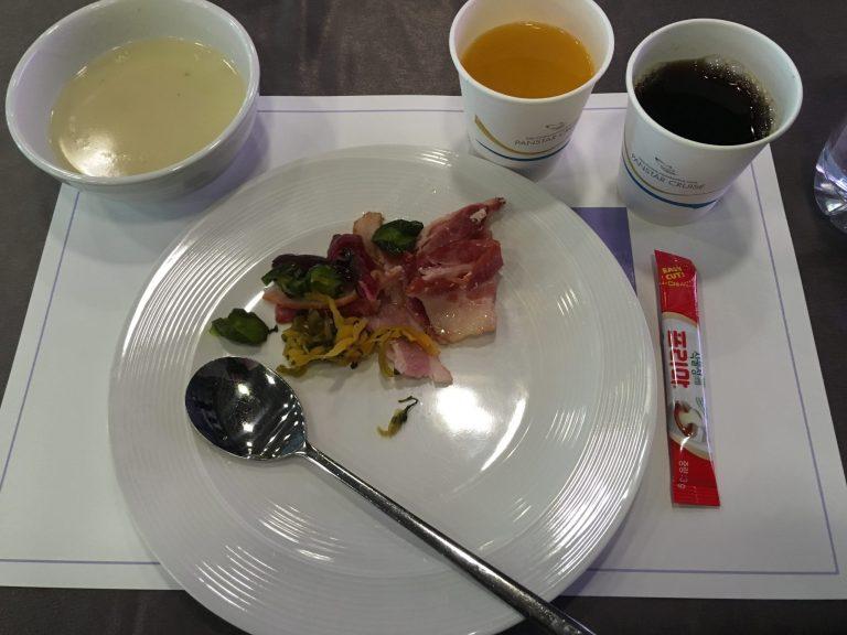 Teller mit asiatischem Frühstück und Getränkebecher